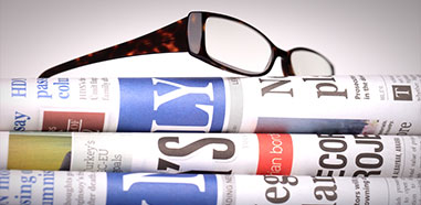 Newspapers with eyeglasses on top