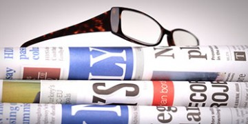 Newspapers staked with eyeglasses on top