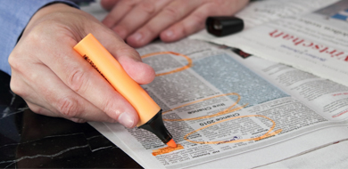 Person searching classified ads with orange highlighter